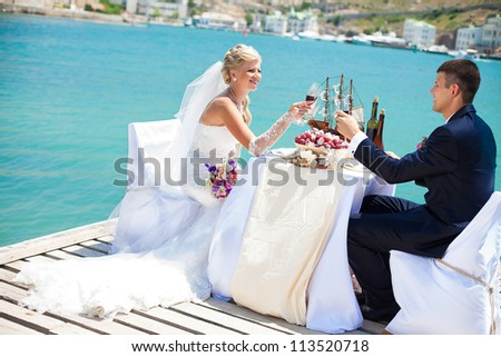 Beautiful couple in love the bride and groom posing on the bridge at the sea at the wedding table decorated with exotic bottles and wooden model ship. Enjoy a moment of happiness and love.