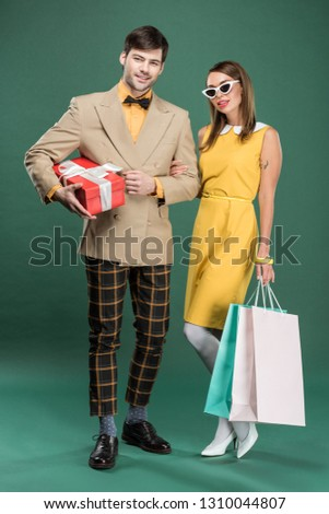 beautiful couple in vintage clothes with shopping bags and gift box on green background