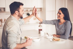 Beautiful couple is eating, giving high five and smiling while sitting in kitchen at home