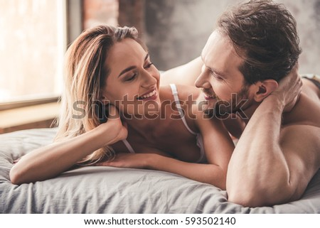 Beautiful couple is looking at each other and smiling while spending time together in bed at home #593502140