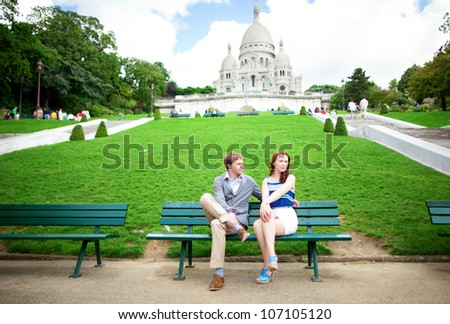 Beautiful couple is sitting on the bench near the Sacre-Coeur basilica in Paris