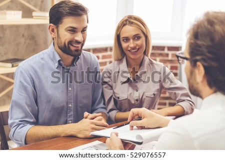 Beautiful couple is talking with realtor, who is showing where to sign the documents