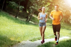 Beautiful couple jogging in nature living healthy