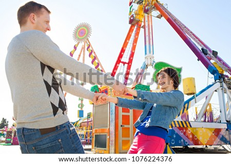 Beautiful couple joyfully holding hands, smiling in vibrant amusement park against sunny sky, colorful rides outdoors. Funfair theme attractions, fun activities, enjoying leisure recreation lifestyle.