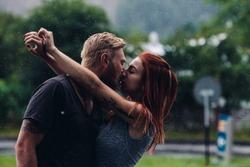 beautiful couple kissing outside in the rain