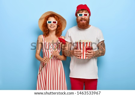 Beautiful couple look happily at screen, watch funny movie, laugh from positive emotions, wear cinema glasses, man holds bucket with popcorn, woman wears hat and dress, stands with red flower