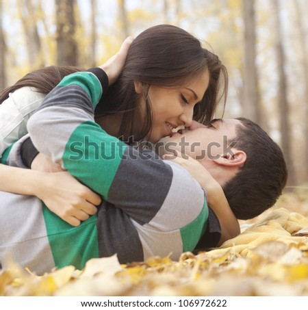 Beautiful couple lying on leaves and hugging