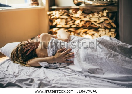 beautiful couple lying together on the bed. the guy hugs the girl in the bed