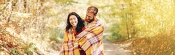 Beautiful couple man woman in love. Boyfriend and girlfriend wrapped in yellow blanket hugging together in park on autumn fall day. Authentic real people. Web banner header for website.