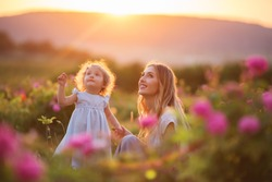Beautiful couple mother and cute little daughter are walking in blossom roses garden over yellow magic sunset lights