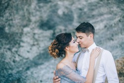 Beautiful couple near the rocks, looking with a smile at each other, hugging wedding day, the bride and groom