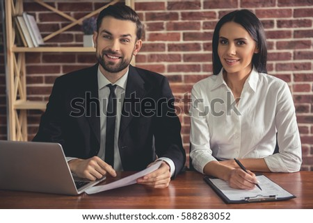 Beautiful couple of employers in suits are looking at camera and smiling while conducting a job interview