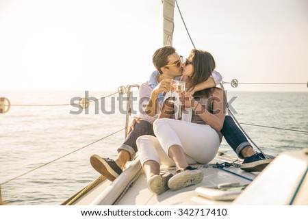Beautiful couple of lovers sailing on a boat - Couple kissing and holding champagne to celebrate - Two fashion models posing on a sailing boat at sunset