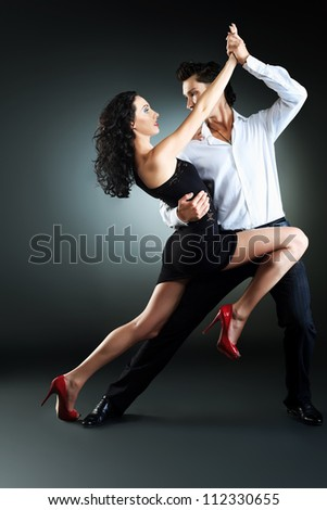 Beautiful couple of professional artists dancing passionate dance.