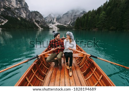 Beautiful couple of young adults visiting an alpine lake at Braies, Italy - Tourists with hiking outfit having fun on vacation during autumn foliage - Concepts about travel, lifestyle and wanderlust Imagine de stoc ©