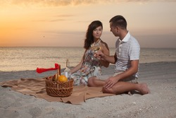 Beautiful Couple On Beach With Wine Picnic during sunset  on sea or ocean. Dawn