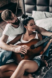 Beautiful couple playing guitar. Handsome young bearded man teaching his girlfriend to play guitar while both sitting in bed at home together