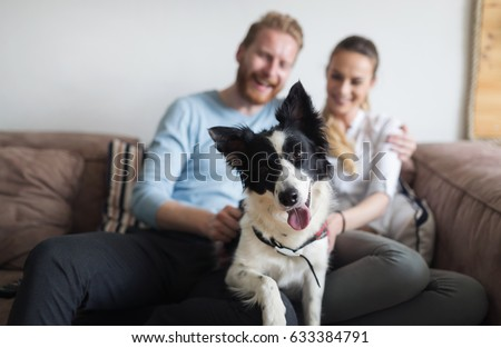 Beautiful couple relaxing at home and loving their pet - Shutterstock ID 633384791