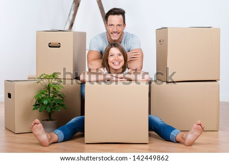 Beautiful couple sitting between many boxes in their new home