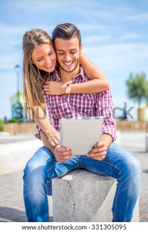Beautiful couple sitting on a bench outdoors and looking at tablet - Lovers having fun with new technology and shopping online #331305095