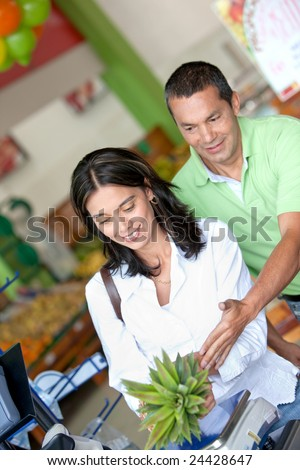 Beautiful couple smiling and buying some fruits at the supermarket - stock photo