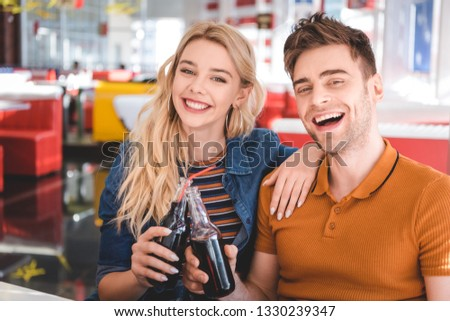 beautiful couple smiling, looking at camera and cheering with glass bottles at cafe