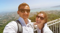 beautiful couple stands on hilltop and makes selfie against pictorial cityscape silhouette and blue ocean bay close view