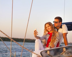 Beautiful couple taking a selfie on a sailing boat at summer sunset