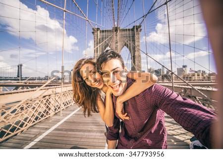 Beautiful couple taking selfie on Brooklyn Bridge, New York - Tourists having fun and photographing NY landmarks