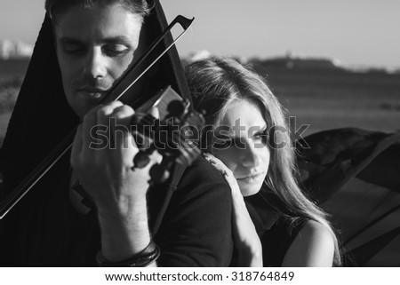 Beautiful couple violinist and young woman together near sea bay. black and white
