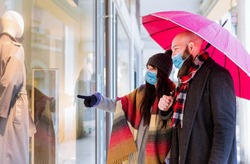 Beautiful couple with an umbrella and winter clothes is talking and smiling while doing shopping in the city in a rainy day.side view of a couple walking past a shop window and looking in for sales.