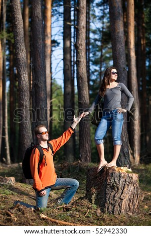 Beautiful couple with backpacks is having fun on the summer forest background. - stock photo