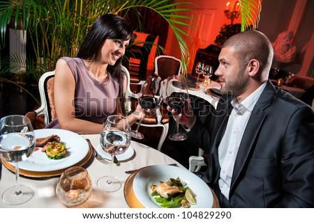 Beautiful couple with glasses of red wine at restaurant on romantic date