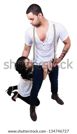 Beautiful couple with sensual look. She's on her knees while he stands staring straight into her eyes