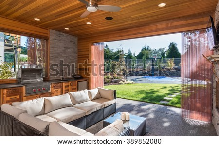 Beautiful covered patio with barbecue, fan, sink, and couch, behind new luxury home. View of landscaped lawn and private basketball court Сток-фото ©