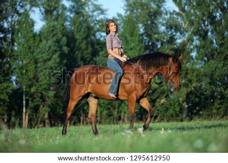Beautiful cowgirl bareback ride her horse in woods glade at sunset