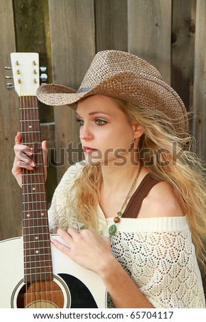 Beautiful cowgirl/singer outdoors enjoying the sun with her white guitar