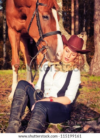 Beautiful  cowgirl with her red horse
