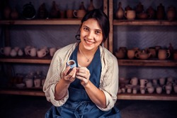 Beautiful craftsman master molding a vase of clay on a potter's wheel. Handcraft.