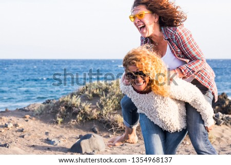 Beautiful crazy caucasian young women carry on eachother having a lot of laughs and fun for friendship - outdoor leisure activity and vacation concept for females friends smiles and gone crazy #1354968137