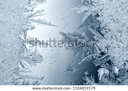 Beautiful crispy frost structure on a window with cold blue gradient light.