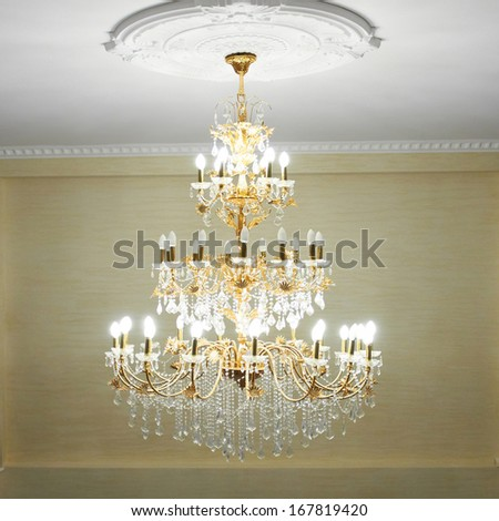 Beautiful crystal ancient chandelier in a hall. Lamp with soft yellow light