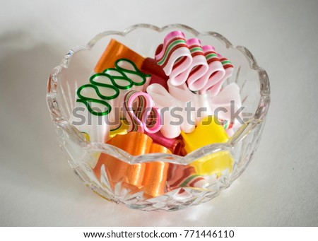 Beautiful crystal bowl is filled with colorful curving ribbon candy on white background. #771446110