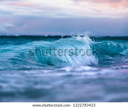 Beautiful Crystal Clear Blue Wave Crashing on Sandy Seashore with Colorful Sunset Sky in Scenic Background in Tranquil Tropical Island Paradise Nature Scene of Maui Hawaii