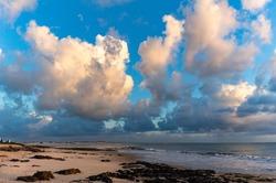Beautiful cumulus clouds lit by the sunrise sun. Water in gaseous form in a cloud.