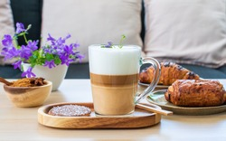Beautiful cup of coffee latte macchiato on wooden table with sweet pasrty, croissant, cofee bread and purple flowers on wooden table in the living room, pastel tone