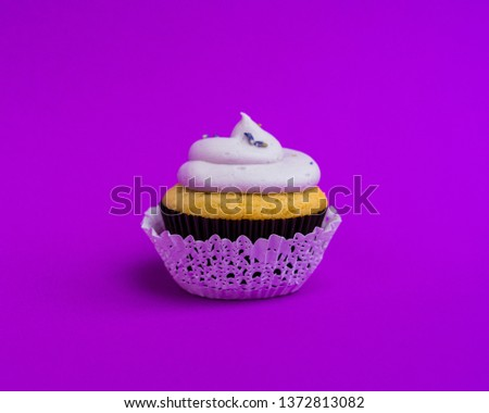 Beautiful cupcake against saturated purple background #1372813082