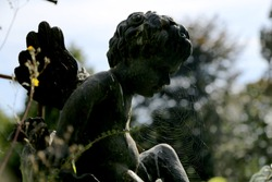 Beautiful Cupid angel statue with wings on back in vintage garden. Cupid angel statue consisting of old dark stone. Interior of abandoned garden is big fine Cupid angel statue, green leaves on trees.