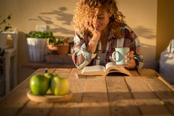 Beautiful curly adult woman read a book outdoor at home int errace or trendy room with wood table and tea or coffee - style lifestyle and concept of people enjoying life at home