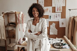 Beautiful curly brunette dark-skinned fashion designer poses in office, leans on table. Young lady in white suit crosses arms and smiles.